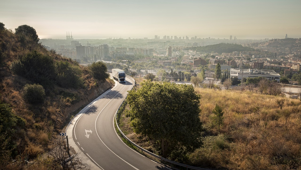 Volvo FH LNG driving away from city.