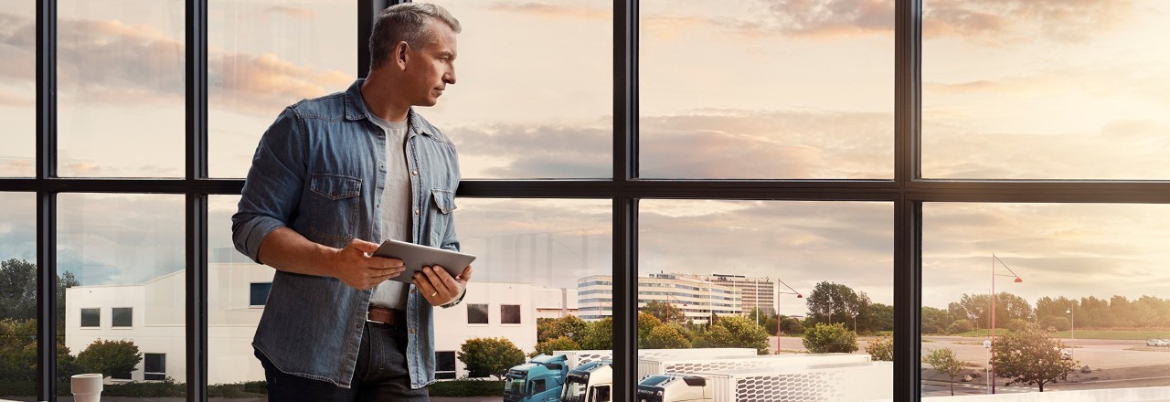 A man holding a tablet stands by a window and looks down over his truck fleet